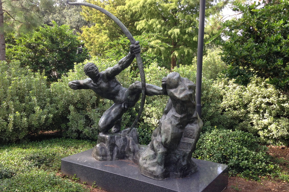 Statue of a muscled figure, crouched, pulling on an enormous bow. Hercules the Archer by Antoine Bourdelle in the New Orleans Museum of Art Sculpture Garden.
