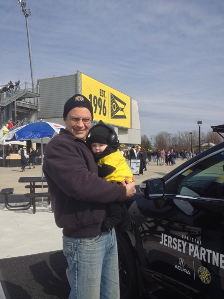 "Me holding Francis at MAPFRE Stadium in front of a ""Est. 1996"" banner"
