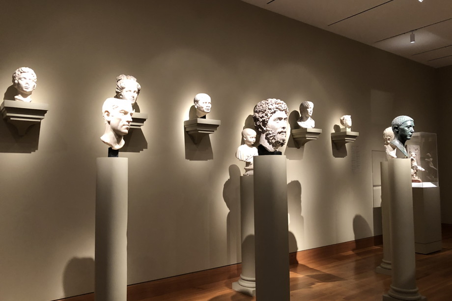 Busts on pedestals in a museum, illuminated so that the heads glow