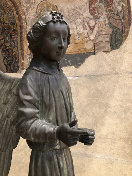 Statue of an angel with a slight smirk, a fresco is in the background