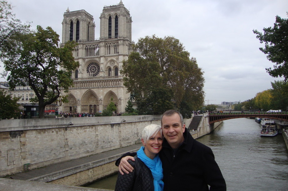 A couple standing in front of a large Gothic church, on a bridge over the Seine
