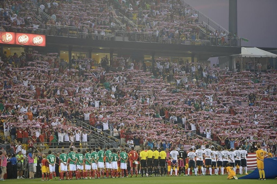Two teams facing a crowd showing USA scarves