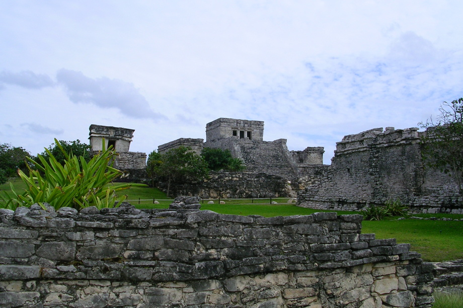 Mayan ruins at Tulum, Mexico - two temples in the distance, lots of old stones and steps surrounded by lush green grass and plants.