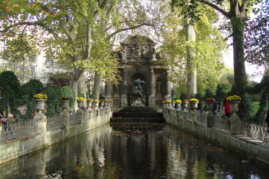 A short canal shaded by trees with flower pots on each side. A large altar with statues is at the far end. The Medici Fountain in the Luxemburg Gardens.