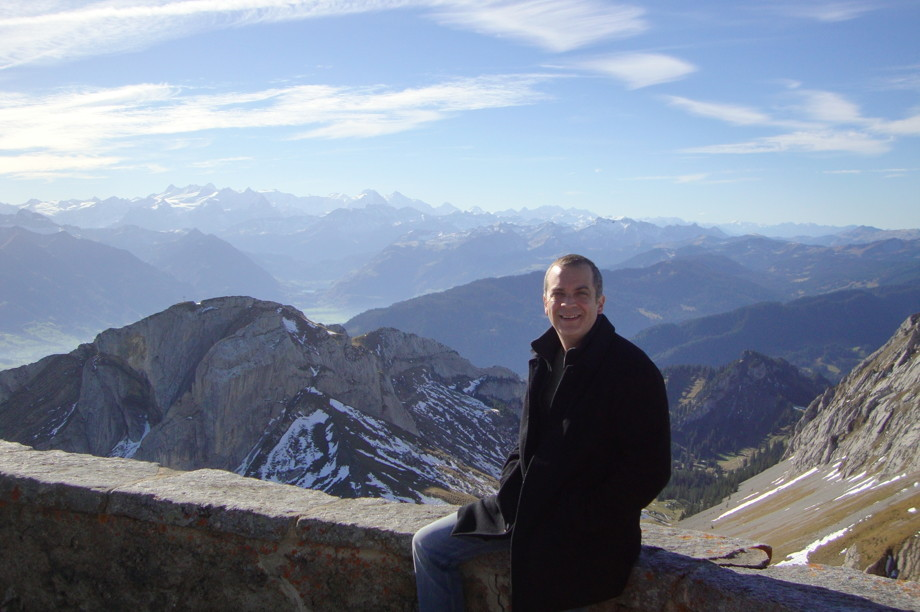 Me on top of a sunny Mt Pilatus in Switzerland, with mountains in the background