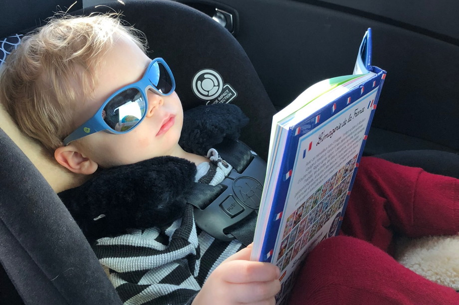 Francis, as a two year-old in a car seat, in sunglasses reading a French picture book