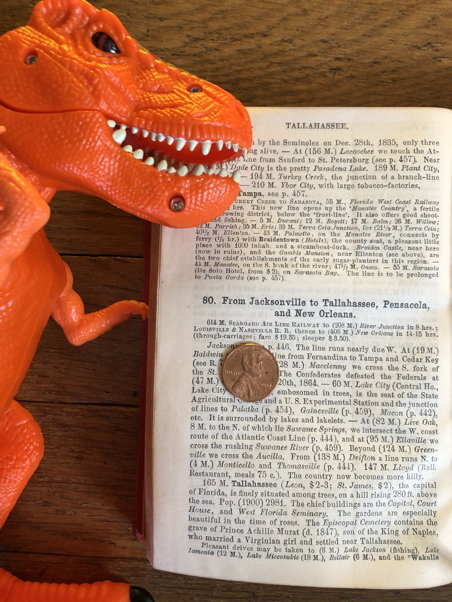 An orange dinosaur inspects a page with small type and a penny on it for scale