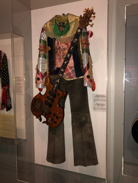 An outrageous shirt in different patterns and fabrics, and a bass guitar, behind plexiglass