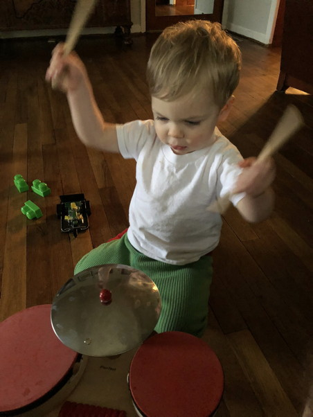 Toddler raising sticks over a toy drum set