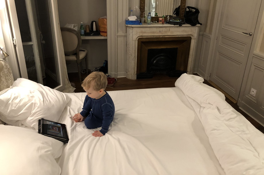 Little boy sitting on a big white bed, looking at a tablet