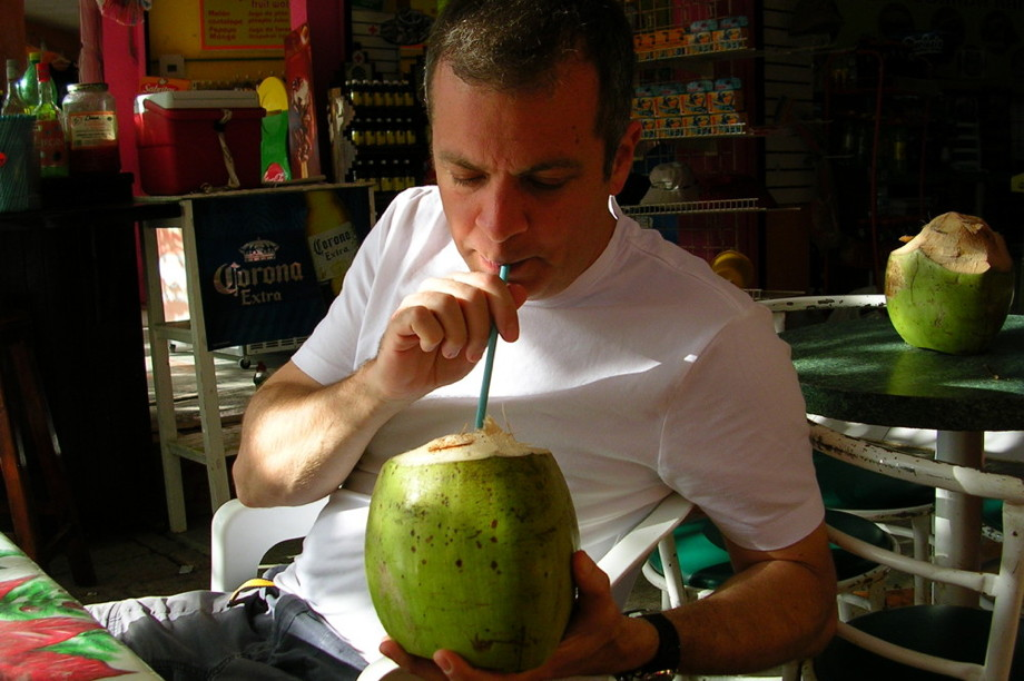 Me in an outdoor restaurant drinking from a green coconut with a long straw
