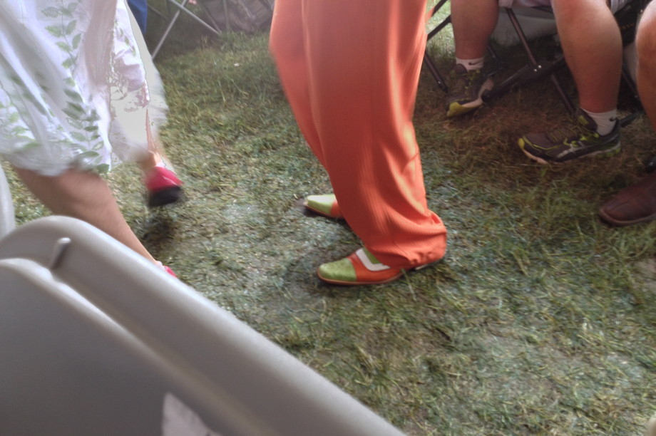 Dude wearing orange pants and orange and green shoes walking on wet grass