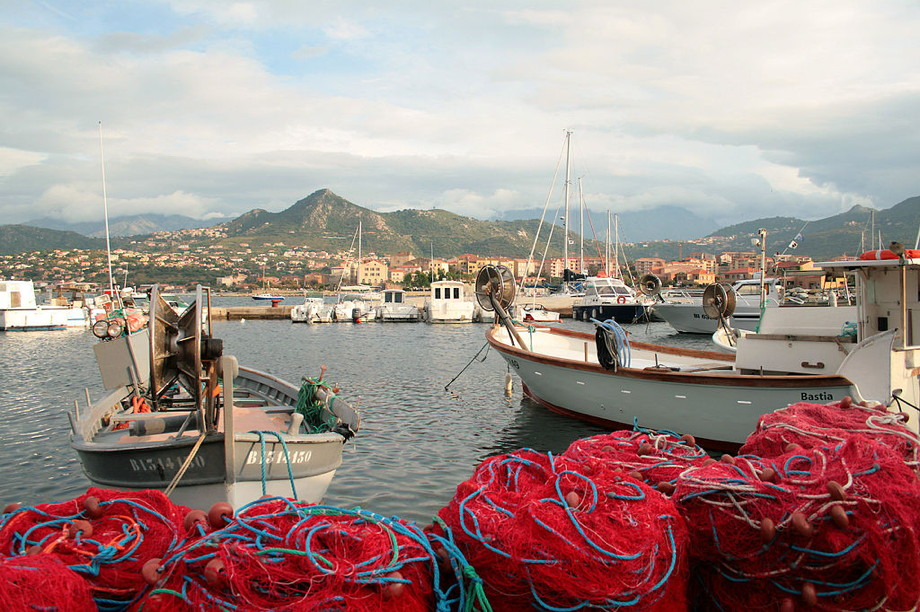 Boats in a harbor with red fishing nets in the foreground and mountains in the background