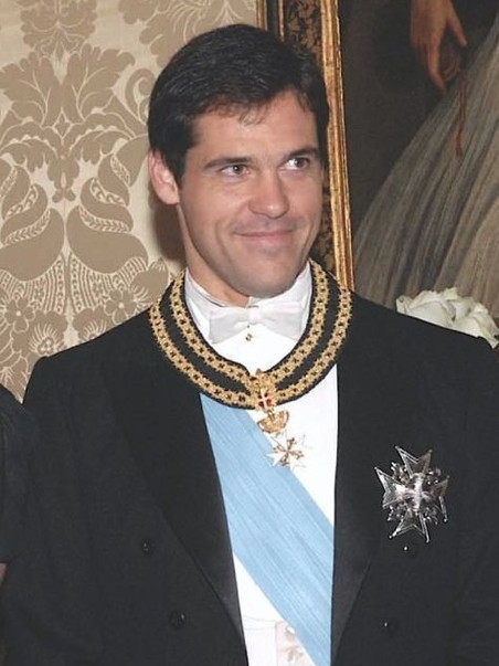 Young virile man in a black coat and sash, wearing medals